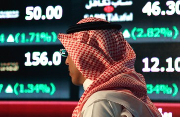 A Saudi man walks at the Tadawul Saudi Stock Exchange, in Riyadh, Saudi Arabia, Monday, June 15, 2015. Saudi Arabia's stock market, valued at $585 billion, opened up to direct foreign investment for the first time Monday, as the kingdom seeks an economic boost amid low global oil prices. (AP Photo/Hasan Jamali)